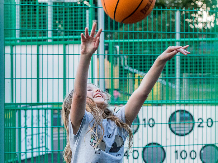 Girl playing basketball on a multi-sports court
