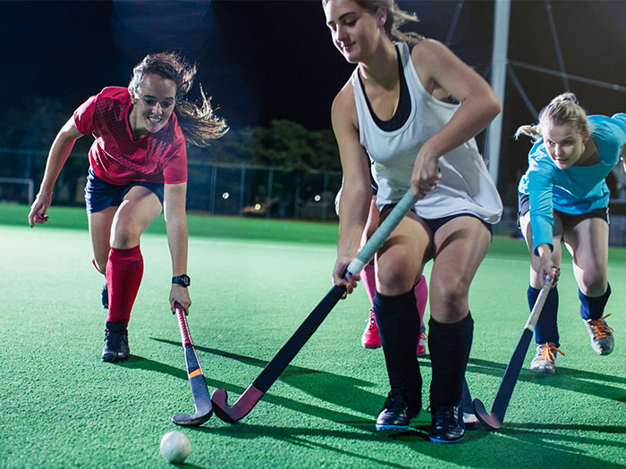 women playing hockey on a multi-sports court