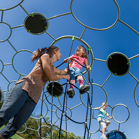 Parent with child playing on a climbing dome